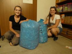Schülerinnen bringen zwei von fünf Säcken voll mit Plastikdeckeln